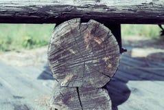 Zbliżenie szczegół craftsmanship prostacka wietrzejąca i pękająca drewniana ławka robić z naturalnych drewnianych bel, z zdjęcia stock