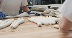 Zbliżenie szczegóły fachowi piekarzi w dużym piekarnia przemysle ugniata ciasto dostawać gotowy gotować chleb w a zdjęcie wideo