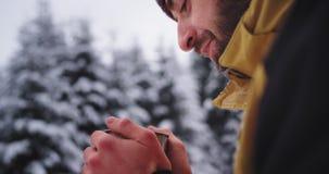 Zbliżenie szczegóły młoda turystyczna czarownica dostają zamarzniętymi w ciężkiej zimie po środku śnieżnego lasu pije niektóre go zbiory wideo