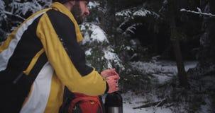 Zbliżenie szczegóły młody turysta trzyma żelazną filiżankę po środku śnieżnego lasu on cieszy się uczucie i widok zdjęcie wideo