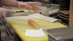 Zbliżenie szef kuchni wręcza narządzaniu japońską karmową rolkę z łososiowym avocado zbiory