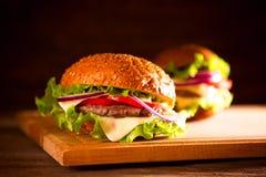 zbliżenie tradycyjni cheeseburger, hamburgeru lub francuza dłoniaki zdjęcie stock