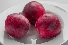 Zbliżenie trzy czerwonego jabłka na bielu talerzu Fotografia Royalty Free