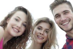 Zbliżenie trzy młodzi ludzie ono uśmiecha się na białym tle Obrazy Stock
