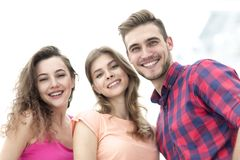 Zbliżenie trzy młodzi ludzie ono uśmiecha się na białym tle Fotografia Stock
