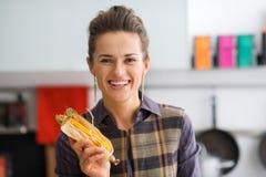 Zbliżenie trzyma up kukurydzanego cob z swój plewą uśmiechnięta kobieta Zdjęcia Stock
