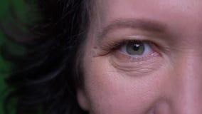 Zbliżenie twarzy przyrodni portret starej caucasian brunetki żeńska patrzeje kamera z tłem odizolowywającym na zieleni zdjęcie wideo