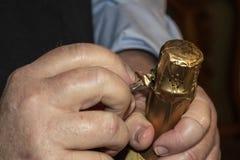 Zbliżenie uprawa mężczyzny otwarcia szampańska butelka - usuwać opakunkową folię zdjęcia stock