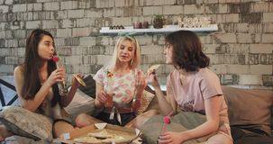 Zbliżenie w nowożytnej sypialni młodych atrakcyjnych damach je pizzę pije niektóre napoje i ciekawić zbiory