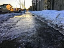 Zbliżenie widok śliski czarny lód zakrywa chodniczek w wczesnym poranku mieszkaniowy neighbourhood podczas zimy zdjęcia stock