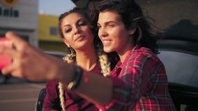 Zbliżenie widok dwa atrakcyjnej młodej kobiety pozuje podczas gdy brać selfie na smartphone obsiadaniu otwarty samochód inside zbiory