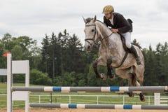 Zbliżenie widok jeździec w czarnej kurtce na białym koniu Zdjęcie Royalty Free