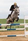 Zbliżenie widok jeździec w czerwonej kurtce na białym koniu Zdjęcie Stock