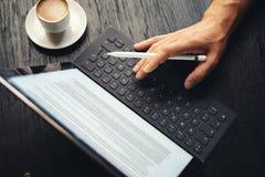 Zbliżenie widok jeden męska ręka pisać na maszynie na elektronicznej pastylka doku staci Mężczyzna pracuje przy biurem i używać Fotografia Royalty Free
