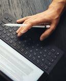 Zbliżenie widok jeden męska ręka pisać na maszynie na elektronicznej pastylka doku staci Mężczyzna pracuje przy biurem i używać Zdjęcie Stock