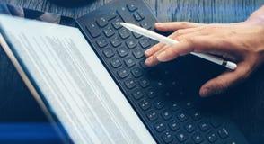 Zbliżenie widok jeden męska ręka pisać na maszynie na elektronicznej pastylka doku staci Mężczyzna pracuje przy biurem i używać Fotografia Stock