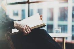 Zbliżenie widok męskie ręki trzyma książkę Młody człowiek relaksuje w domu podczas gdy siedzący w rocznika krześle Selekcyjna ost Zdjęcie Stock