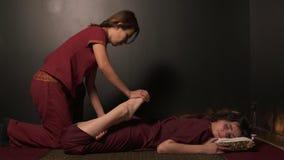 Zbliżenie widok młoda kobieta ma tajlandzkiego masaż w zdroju żeńskim massagist w kimonie Tajlandzki massagist rozciąga zbiory