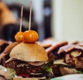 Zbliżenie widok Mali Handmade hamburgery na stole z zalewami, pomidorami, wieprzowin Cutlets i sałatkami jako składniki, - kuchni obrazy stock