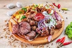 Zbliżenie widok na secie piec na grillu mięso i warzywa słuzyć na drewnianej porcji desce na stole z ziele pikantność Grill wiepr obraz royalty free