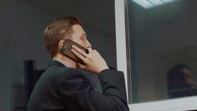 Zbliżenie widok od plecy patrzeje przez okno mężczyzna podczas gdy mieć wiszącą ozdobę wzywa telefonu komórkowego wieczór biuro zbiory wideo