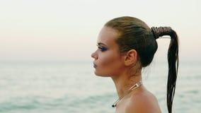 Zbliżenie widok seksowna kobieta z fachowym złotym makeup i mokry ponytail odprowadzenie wodą na plaży wtedy zdjęcie wideo
