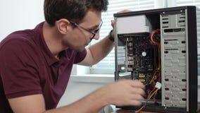Zbliżenie widok skoncentrowany komputerowej usługa pracownik załatwia łamanego komputer w ulepszać i biurze w szkłach zdjęcie wideo