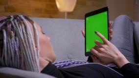 Zbliżenie widoku tylny krótkopęd młoda caucasian modniś kobieta z dreadlocks używać pastylkę z zieleń ekranem z reklamą dalej zdjęcie wideo