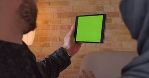 Zbliżenie widoku tylny krótkopęd młoda rozochocona muzułmańska para używa pastylkę z zieleń ekranem z reklamą na nim zdjęcie wideo