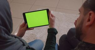 Zbliżenie widoku tylny krótkopęd młoda rozochocona muzułmańska para w niedawno kupującym mieszkaniu używać pastylkę z zieleń ekra zdjęcie wideo