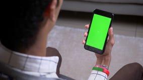 Zbliżenie widoku tylny krótkopęd trzyma telefon z zieleń ekranem indoors samiec ma wideo wezwanie z ręką w mieszkaniu zdjęcie wideo