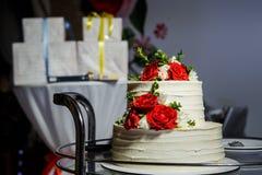 zbliżenie wielopoziomowy tort z różami na szklanej tacy przeciw prezentom fotografia stock