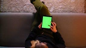 Zbliżenie wierzchołka krótkopęd ładna dziewczyna używa pastylkę z zieleń ekranem i surfujący sieć podczas gdy siedzący na kanapie zdjęcie wideo