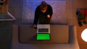 Zbliżenie wierzchołka krótkopęd ładna kobieta używa laptop w wygodnym mieszkaniu podczas gdy siedzący na dywanie indoors zbiory