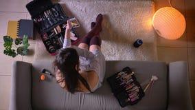 Zbliżenie wierzchołka krótkopęd młoda atrakcyjna kobieta stosuje makeup używać telefonu lustra obsiadanie na leżance w ślicznych  zdjęcie wideo