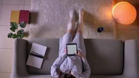 Zbliżenie wierzchołka krótkopęd młodego atrakcyjnego żeńskiego nastolatka czytelniczy ebook na pastylce z zielonym chroma ekranu  zbiory wideo