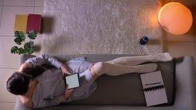 Zbliżenie wierzchołka krótkopęd młodego atrakcyjnego żeńskiego nastolatka czytelniczy ebook na pastylki obsiadaniu na leżance w ś zbiory wideo