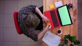Zbliżenie wierzchołka krótkopęd młody caucasian biznesmen pracuje na laptopie z zieleń ekranem i robi przypomnieniu wokoło zdjęcie wideo