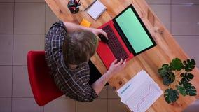 Zbliżenie wierzchołka krótkopęd młody caucasian biznesmen robi zakupy online na laptopie z zieleń ekranem na biurku w zdjęcie wideo