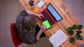 Zbliżenie wierzchołka krótkopęd młody caucasian biznesmen robi zakupy online na pastylce z kartą kredytową przed laptopem zdjęcie wideo