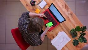 Zbliżenie wierzchołka krótkopęd młody caucasian biznesmen robi zakupy online na telefonie z kartą kredytową wewnątrz przed laptop zbiory