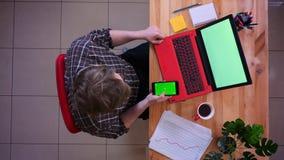 Zbliżenie wierzchołka krótkopęd młody caucasian biznesmena scrolling na telefonie z zieleń ekranem przed laptopem z zbiory