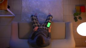 Zbliżenie wierzchołka krótkopęd młody męski ogląda TV i używać app na telefonie z zieleń ekranem jako pilota do tv obsiadanie zbiory