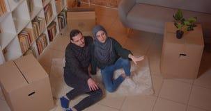 Zbliżenie wierzchołka krótkopęd młody rozochocony muzułmański pary obsiadanie na podłodze ono uśmiecha się szczęśliwie w niedawno zbiory wideo