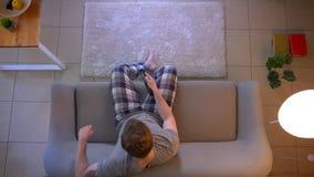 Zbliżenie wierzchołka krótkopęd potomstwa niezobowiązująco ubierał męskiego ogląda TV jest relaksującym obsiadaniem na leżance i  zdjęcie wideo
