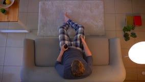 Zbliżenie wierzchołka krótkopęd potomstwa niezobowiązująco ubierał męskiego ogląda TV obsiadanie na leżance i pić piwo dostaje da zdjęcie wideo