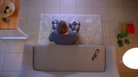 Zbliżenie wierzchołka krótkopęd potomstwa niezobowiązująco ubierał męskiego ogląda TV obsiadanie na leżance i pisać puszkowi prze zbiory wideo
