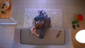 Zbliżenie wierzchołka krótkopęd potomstwa niezobowiązująco ubierał męskiego ogląda TV obsiadanie na podłodze i pisać puszkowi prz zbiory