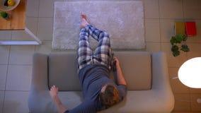 Zbliżenie wierzchołka krótkopęd potomstwa niezobowiązująco ubierał męskiego ogląda TV podczas gdy siedzący na leżance chodzących  zbiory wideo