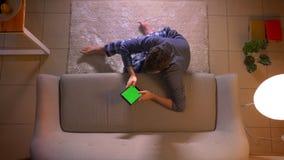 Zbliżenie wierzchołka krótkopęd texting na pastylce z zieleń ekranem młody człowiek podczas gdy siedzący na podłodze indoors przy zbiory wideo